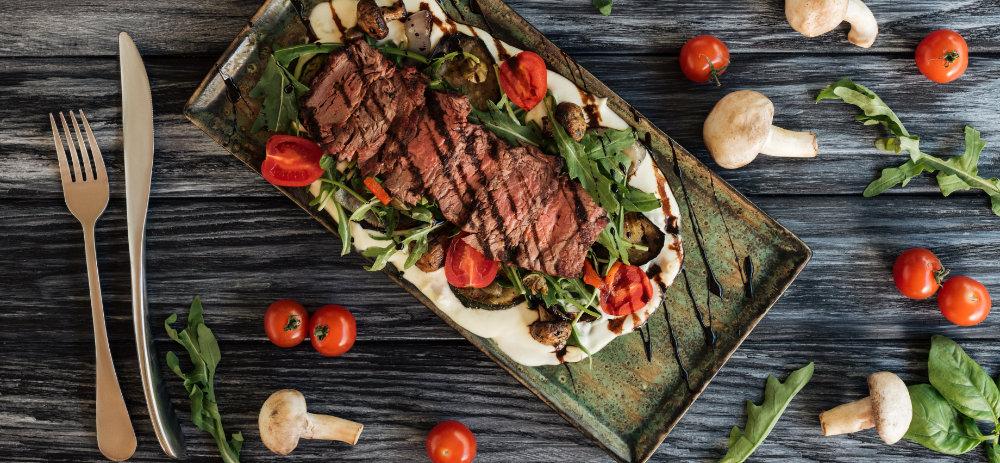 Steak zubereitet mit Auberginen, Tomaten, Rucola und Balsamico